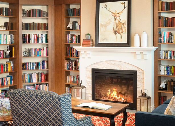 Library with fireplace at Amica Stoney Creek senior residence.