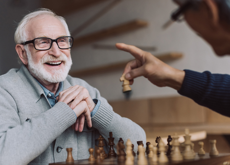 Happy Amica senior playing chess at Amica retirement living residence.