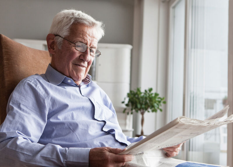 Male senior resident reading newspaper at Amica senior living residence.